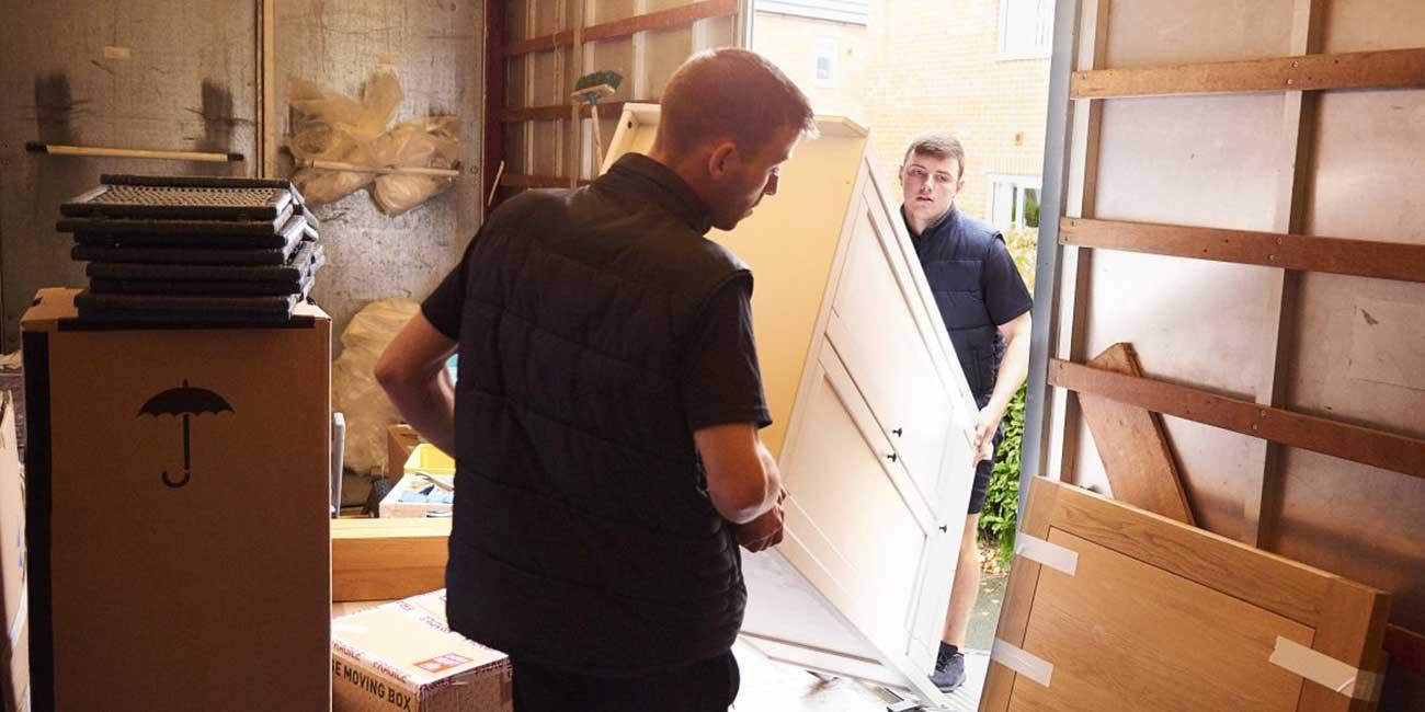 Men carrying items into a van
