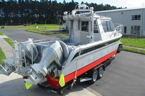 Small boat 7.3m Bladerunner power cat on trailer coupled to Massey Fer...